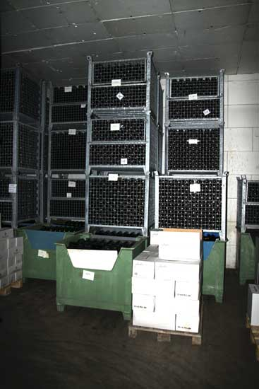 Unlabelled wines stored in barred boxes